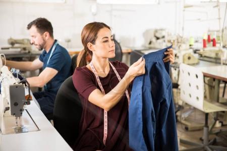 Seamstress looking at a finished shirt