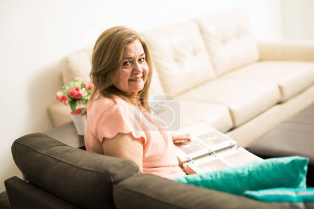 Photo for Attractive aged grandmother proud of her past life sitting on sofa in living room - Royalty Free Image