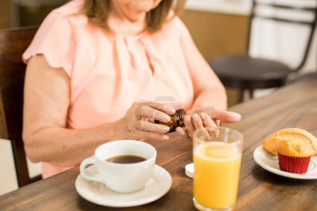 Granny taking medication with breakfast
