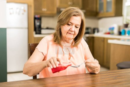 Lady taking spoon of sore
