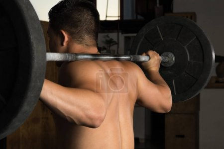 Photo for Rear view of a strong shirtless man holding a barbell up while doing squats in a gym - Royalty Free Image