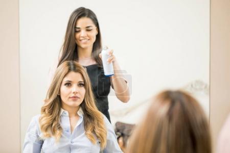 Hairdresser using some spray
