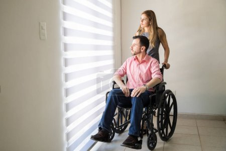 Sad man in a wheelchair with his partner