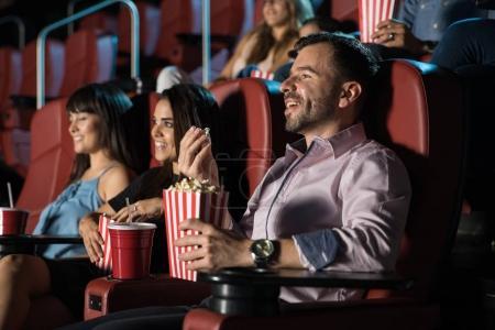 Photo pour Petite foule de gens assis dans un cinéma et bénéficiant d'un film. - image libre de droit