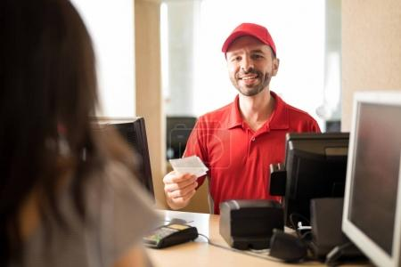 Worker handing tickets at movie theater