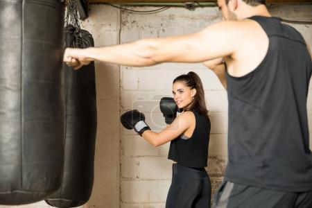 Photo pour Jeune et jolie boxer femelle de formation avec un sac de boxe et d'écouter les conseils de son entraîneur - image libre de droit