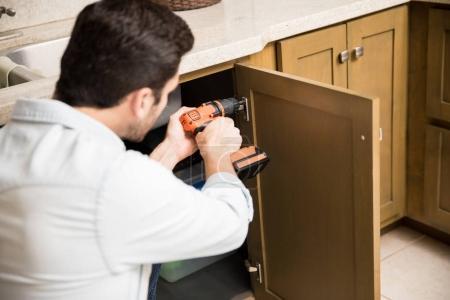 Handyman fixing a kitchen cabinet