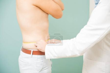 Doctor measuring a patient's waist