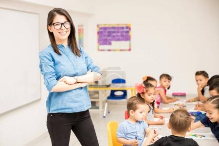 Nerdy preschool teacher standing in a classroom full with students and smiling