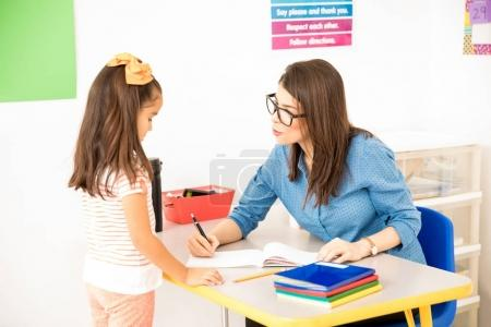 Nerdy preschool teacher wearing glasses and grading the work of one of her students while sitting in her desk