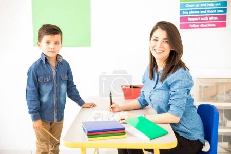Attractive Hispanic preschool teacher grading a student's work while sitting on her desk in a classroom