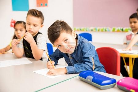 Portrait of a Hispanic little boy doing some basic math exercises in preschool and making eye contact