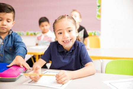 Portrait of a cute Hispanic little girl attending preschool and smiling with a toothless grin