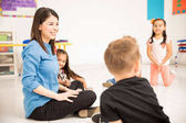 Beautiful preschool teacher having fun with her pupils in the classroom
