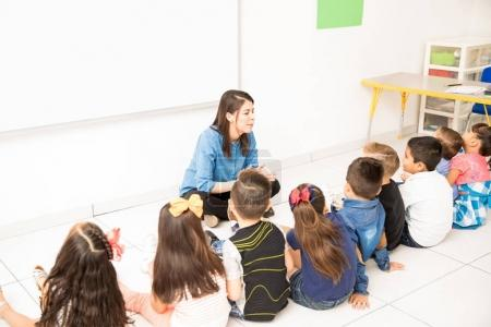 Group of preschool students and their teacher sitting in the classroom floor and learning