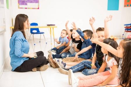 Profile view of a group of preschool students raising their hands and trying to participate at school