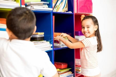 Portrait of a gorgeous Latin preschool girl looking for some of her books in front of a classroom locker and smiling