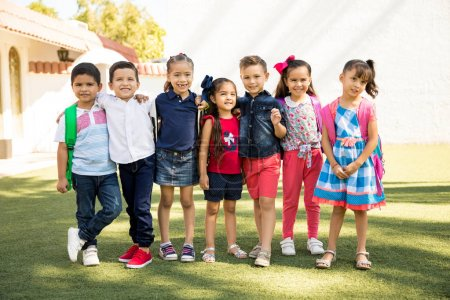 Full length view of a group of kids standing outside of preschool on a sunny day and smiling