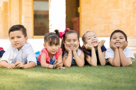 Cute group of preschool friends lying on the grass and smiling, having a good time together