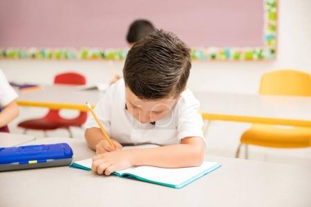 Male preschooler wearing uniform and working on a writing assigment in the classroom
