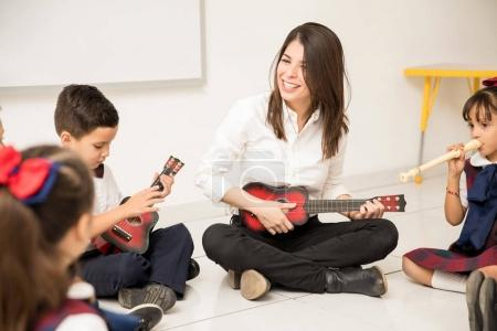 Fun female preschool teacher playing a guitar and teaching some music to her students