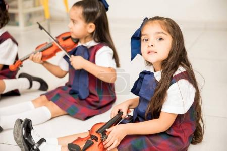 Good looking little girl holding a small violin and making eye contact during her music class in preschool