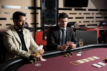 Serious looking men betting a lot of money on a poker game in a casino