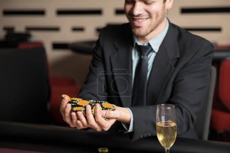 Closeup of a happy young man in a suit holding a bunch of chips after winning a poker game in a casino