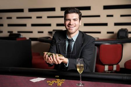 Happy young man sitting at a casino table with hand full of chips after winning a poker game