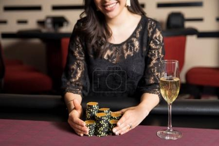 Closeup of a happy woman holding a bunch of poker chips after winning a game at a casino