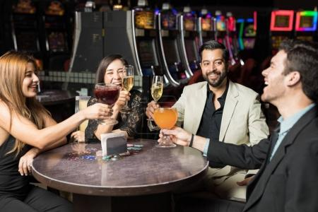 Four friends sitting in a restaurant table in a casino and celebrating making a toast with some drinks