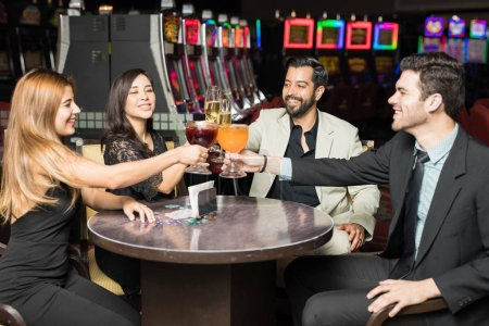 Cheerful Latin friends raising their glasses and making a toast to celebrate winning at a casino