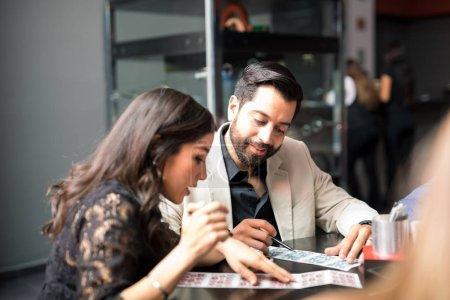 Good looking young Latin couple playing bingo at a casino and having fun
