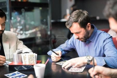 Young man with a beard concentrating on his numbers while playing casino lottery