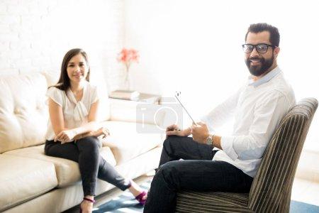 Photo pour Psychologue masculin professionnel avec female client assis sur le canapé dans son bureau - image libre de droit