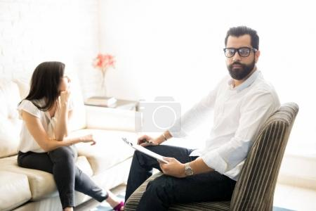 Professional therapist with female patient in office