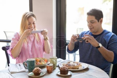 Couple taking photographs of food on cafe table with their mobile phones