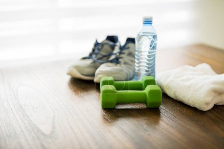 Fitness and active lifestyles concept. Dumbbells, sport shoes,  bottle of water and towel on wooden table