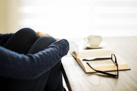 Mujer sentada junto a una mesa con un libro y ojo gafas
