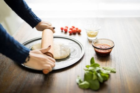 Close up of woman hands preparing pizza base with rolling pin