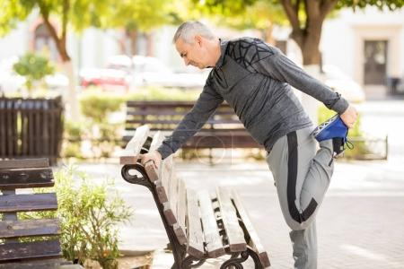 Hispanic mature man getting ready to go for a run in the park and doing stretching exercises on the bench
