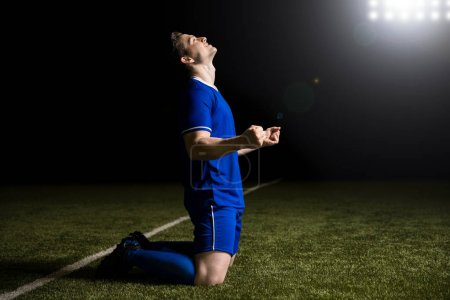 Happy young soccer player celebrates after scoring a goal during match in stadium