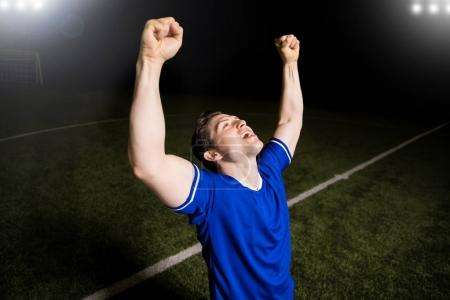 Cheerful male footballer raising his arms and celebrating his victory in the stadium