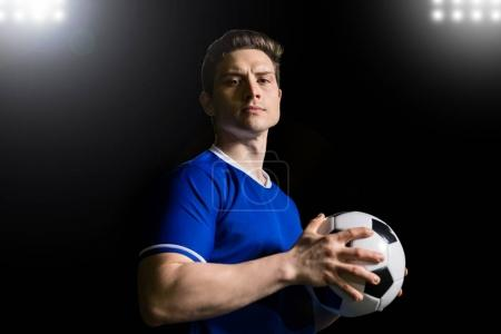 Portrait of handsome young football player in blue uniform holding a ball and making en eye contact on stadium