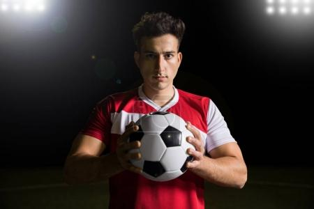 Portrait of good looking young sportsman holding a soccer ball and making en eye contact on field