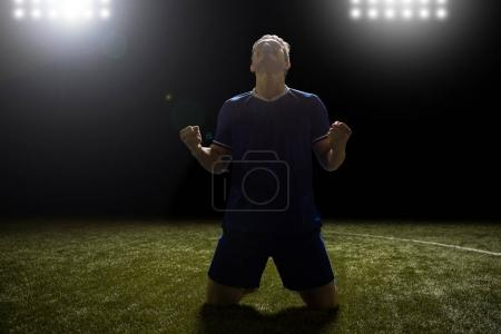 Happy young footballer on knees in stadium celebrating a win