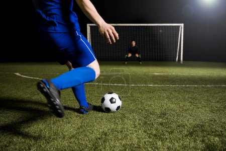 Legs of a soccer player about to kick off the soccer ball from the green grassy sports field towards the goalpost