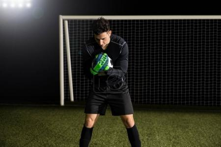 Fit young soccer goalkeeper catching a ball at football goal on field