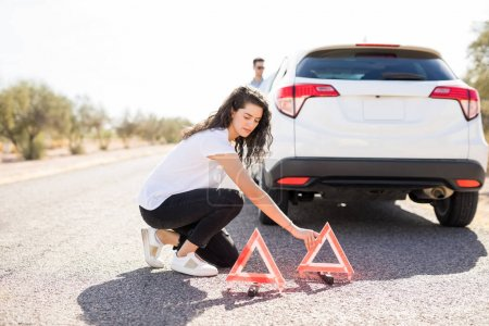 Photo for Woman putting red emergency stop triangle signs on road near broken car - Royalty Free Image