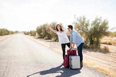 couple of tourists with luggage hitchhiking on countryside road